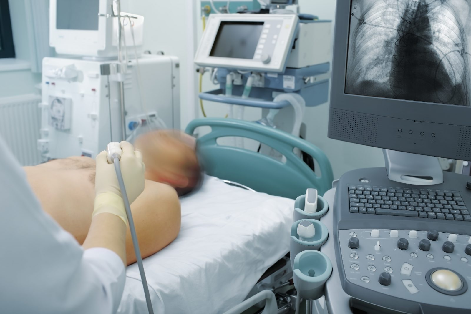 Medical personnel use an ultrasound machine to check a patient's lungs.