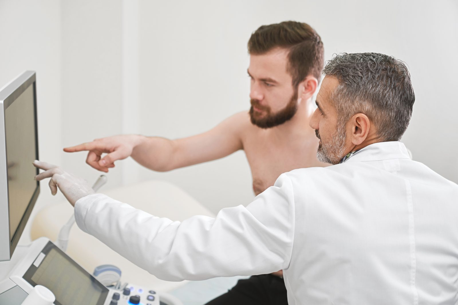 A modern private clinic with ultrasound machine – patient consultation with doctor.